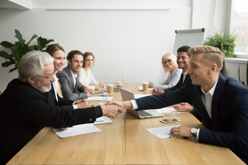 Senior Investor Handshaking Young Man in a meeting