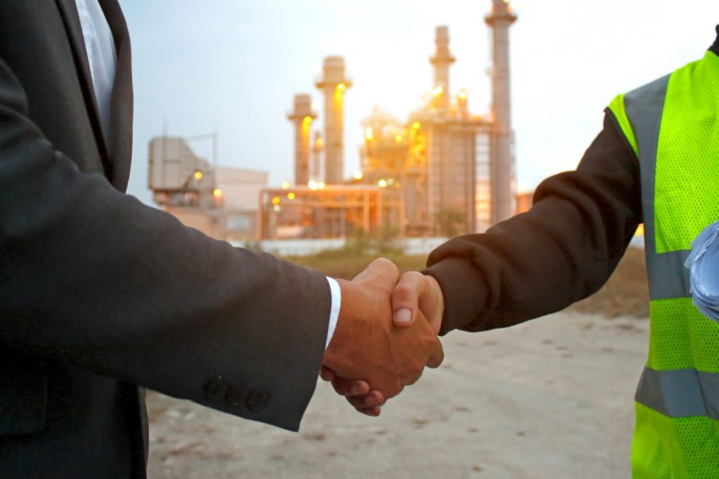 Two businessmen shaking hands in front of a factory