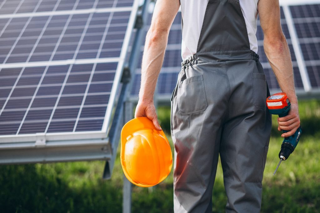 A worker fixing a solar panel