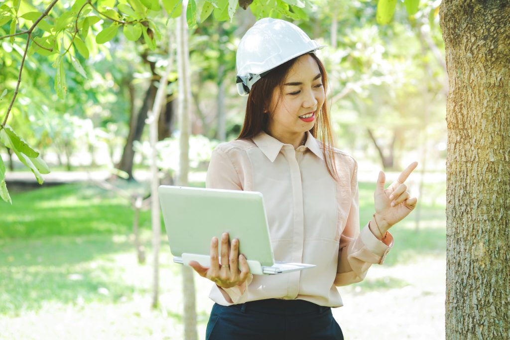 Woman wearing white hard hat carrying a laptop in a bataan technology park