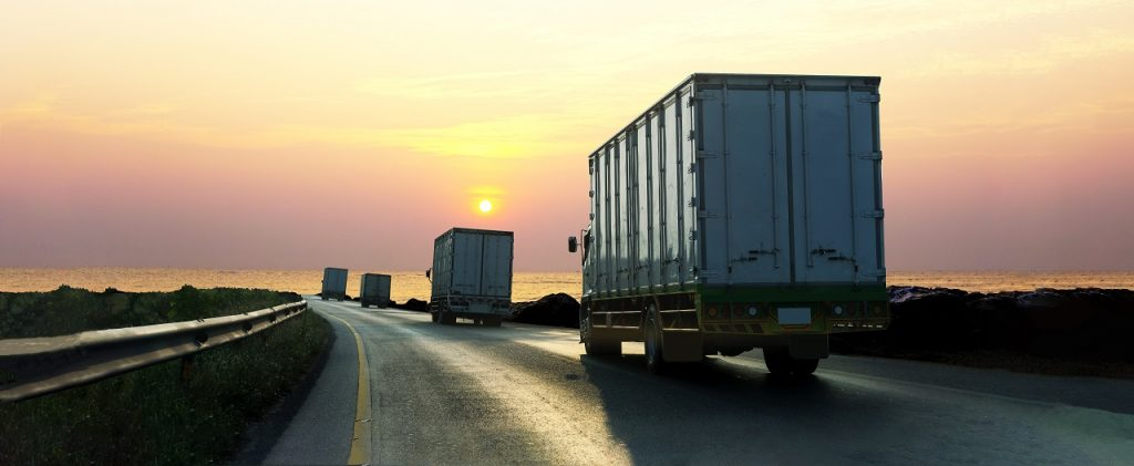 Trucks on a road while the sun sets behind