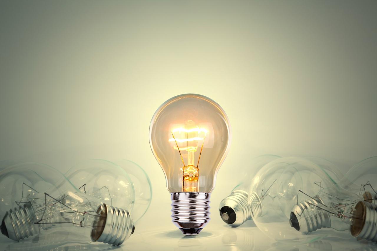 Graphics of a single lit lightbulb surrounded by unlit lightbulbs