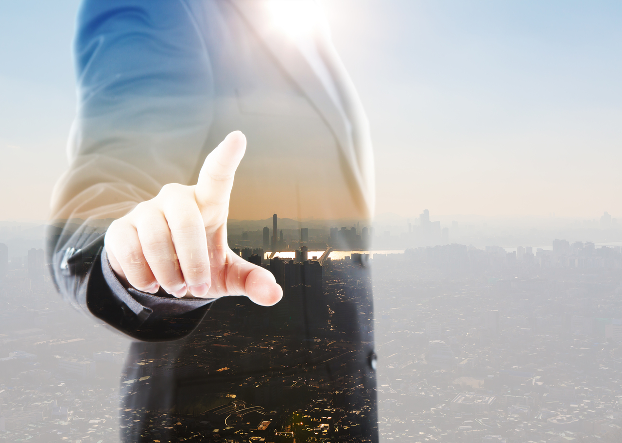 A business man pointing to a city from industrial park