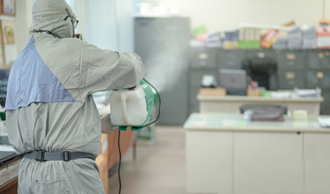 A man disinfecting an office