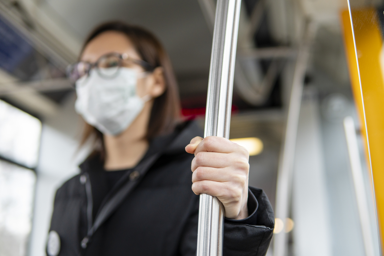 A woman in a face mask on a bus