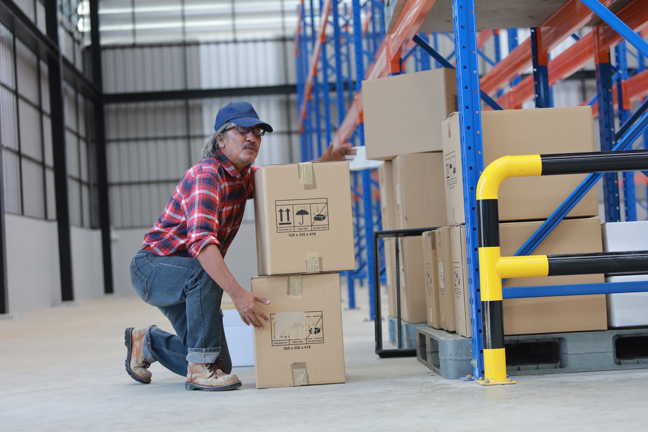 A factory worker with back pain due to lifting a box