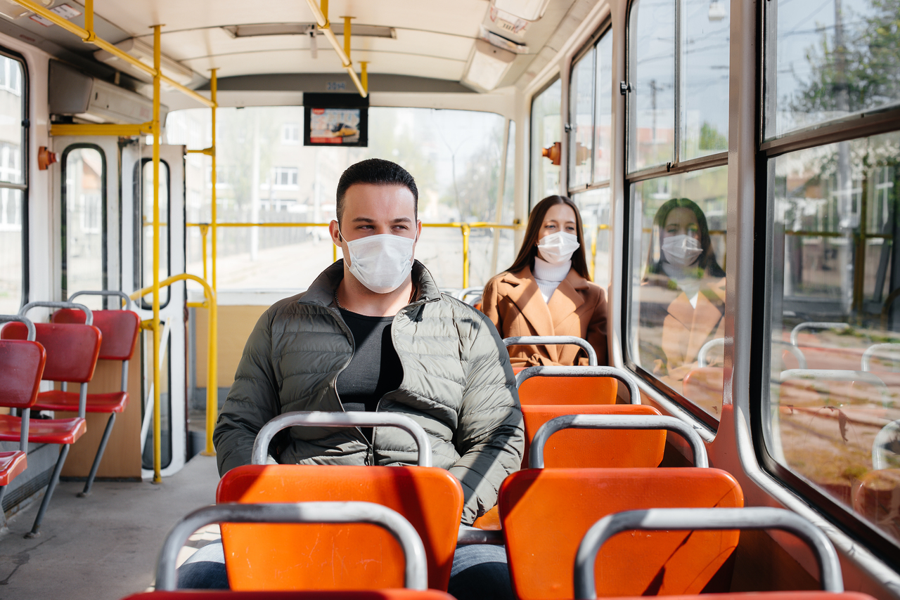 Two people wearing face masks on a bus