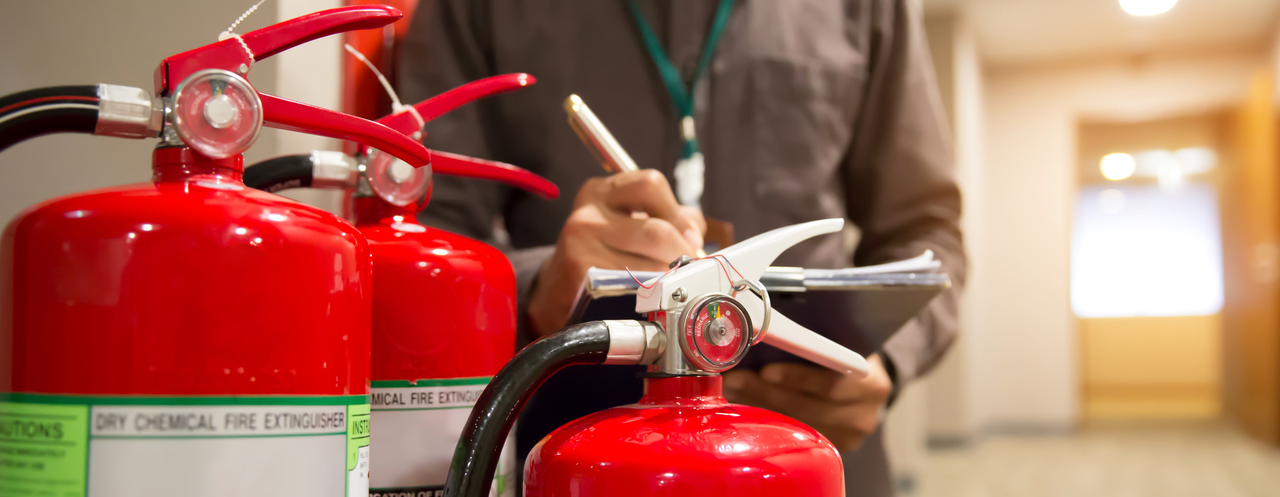 An employee checking fire extinguishers