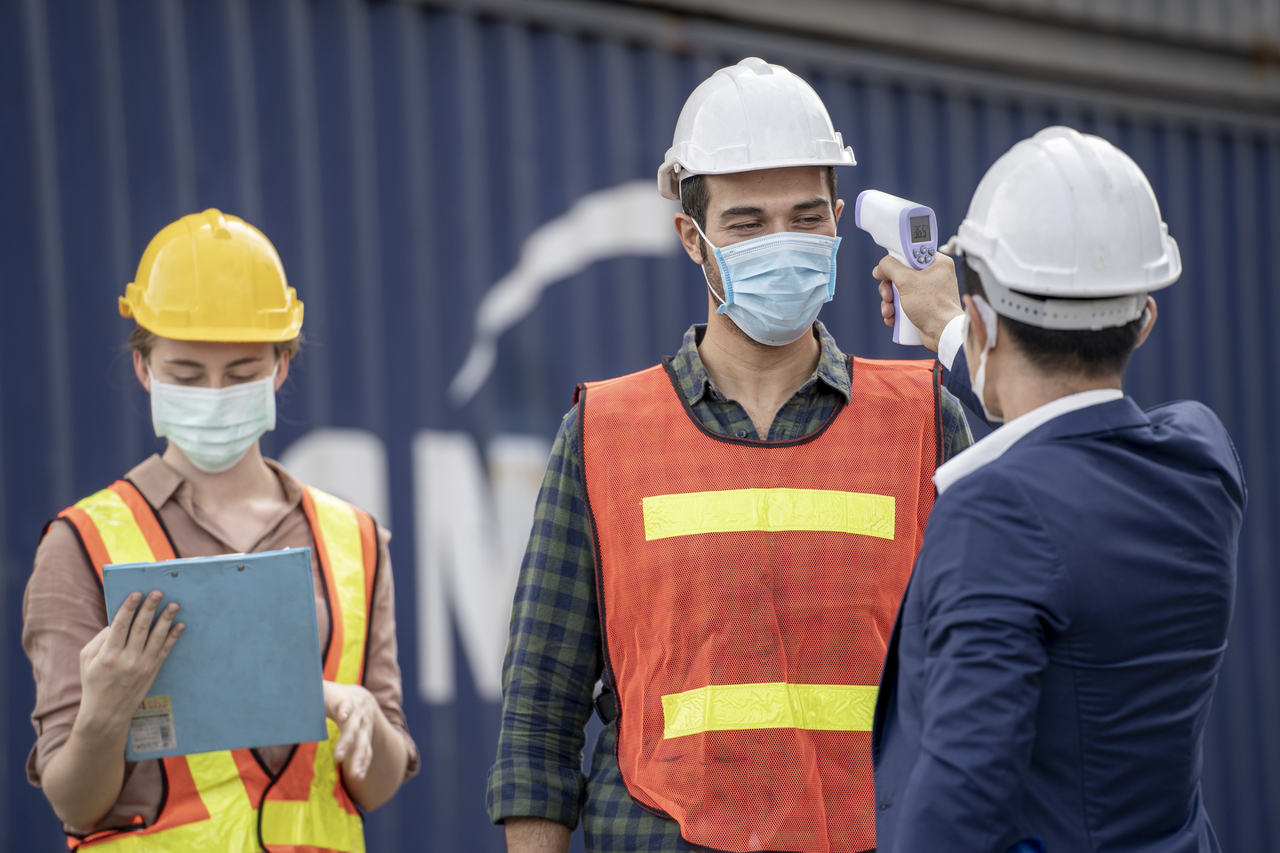 Industrial worker's temperature being checked