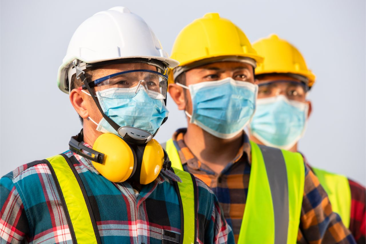 Manufacturing workers with face masks and personal protective equipment